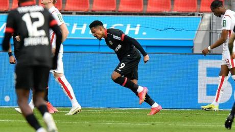 Leverkusens Stürmer Leon Bailey (M) juebelt über sein Tor zum 1:0.