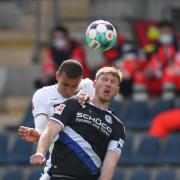 Bielefelds Fabian Klos (vorne) im Kopfballduell mit Hoffenheims Kevin Akpoguma.