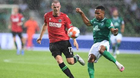 Werders Felix Agu (r) kommt vor Hannovers Marvin Ducksch an den Ball.