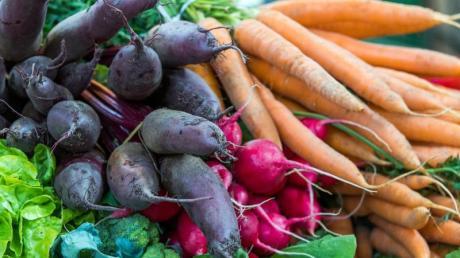 Frisches Gemüse liegt an einem Verkaufsstand in einer Markthalle.