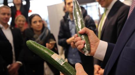 Gerd Müller (CSU), Bundesentwicklungsminister, informiert sich in einem Berliner Lidl-Supermarkt zu fairem Einkauf und fragt bei einem gemeinsamen Supermarkt-Rundgang mit Journalisten, warum Bio-Gurken in Plastikfolie eingepackt sein müssen. Foto: Wolfgang Kumm/dpa