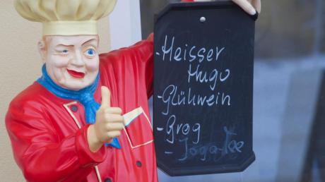 Eine Koch-Figur fungiert als Werbeträger für eine Gaststätte und wirbt für heißen Hugo, Glühwein und Grog.