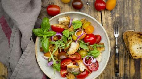 Ruckzuck ist aus altem Brot ein Brotsalat gemacht. In Italien wird er Panzanella genannt und ist meist aus geröstetem Ciabatta, roten Zwiebeln, Tomaten und Basilikum.