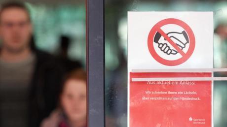 «Aus Aktuellem Anlass: Wir schenken Ihnen einen Lächeln, aber verzichten auf den Händedruck» steht auf einer Glastür einer Sparkasse.