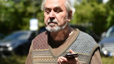 Manfred Scharbach, Vorsitzender vom Allgemeinen Blinden- und Sehbehindertenverein, hört der Sprachausgabe seines Handys.