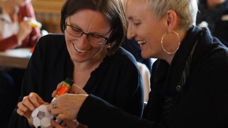 Zusammen klebt es sich leichter: Iris Hildensperger (links), pädagogische Mitarbeiterin des Schulmuseums, und Grundschullehrerin Ute Zimmermann bauen aus einem Bastelbogen einen Fußball.