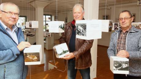 In Gundremmingen eröffnet am Freitag eine Sonderausstellung mit Ansichten des Ortes von früher und heute. Sie sind an Würfeln befestigt, die von der Decke hängen. Von links: Hans Joas, Georg Endris und Josef Eberle.