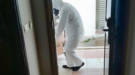 In Schutzkleidung wird in Quarantäne befindlichen Gästen eines Hotels in Nordzypern Essen gebracht. Ein Ehepaar aus Bibertal ist unter ihnen.