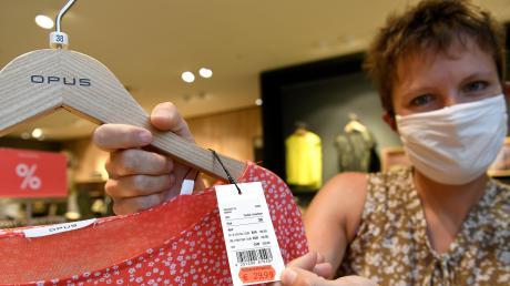 Judith Ganser vom Modehaus Schild in Günzburg zeigt ein stark reduziertes Kleidungsstück. Das Unternehmen gibt die Mehrwertsteuer-Absenkung bis zum Jahresende in Form von Rabattcoupons an die Kunden weiter.