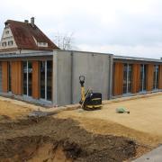 Das Flachdach-Gebäude wurde in einer Holzständer-Stahlbeton-Kombination errichtet. Noch gibt es Restarbeiten im Außenbereich.