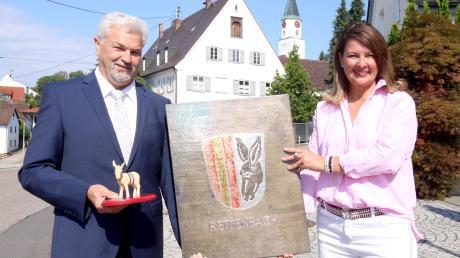 """Rettenbach, Harthausen und Remshart haben sich vor 50 Jahren zusammengeschlossen. Bürgermeisterin Sandra Dietrich-Kast und Zweiter Bürgermeister Alexander von Riedheim mit dem Wappen der Gemeinde sowie dem Wappentier, dem Esel """"Andi"""", vor dem Rettenbacher Schlössle."""