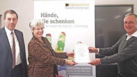 Kolping-Diözesanpräses Wolfgang Kretschmer (rechts) überreicht Claudia und Roland Kober die Gründungsurkunde ihrer Zustiftung.