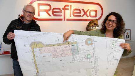Reflexa-Chefin Miriam Albrecht und Betriebsleiter Manfred Gross zeigen auf einem Plan, wo die Neubauten am Stammsitz in Rettenbach entstehen werden (die rosa eingezeichnete Fläche ist der erste Bauabschnitt, der zweite ist der graue Bereich rechts daneben).