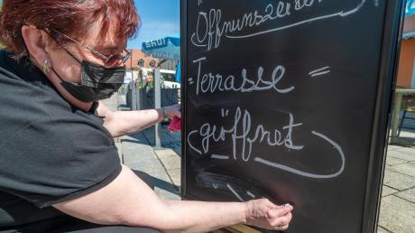 """Das hier ist ein aktuelles Foto und nicht etwa eines aus dem Archiv. """"Terrasse = geöffnet"""", schreibt diese Frau auf ein Hinweisschild vor einem Café. Kleiner Haken an der Sache: Die Außengastronomie, die hier betrieben wird, steht in der oberpfälzischen Stadt Tirschenreuth und nicht etwa im Landkreis Günzburg."""