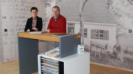 Elke und Norbert Alt von der Firma Inspiration Alt. Sie stehen vor einem Bild der einstigen Schreinerei, die 1885 in Bubenhausen gegründet wurde.