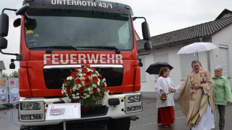 Das neue Löschfahrzeug LF10 in Unterroth löst seinen 29 Jahre alten Vorgänger ab. Pfarrer Johann Wölfle versäumte nicht, dem vielen Wasser vom Himmel auch noch das aus dem Unterrother Weihwasserkessel hinzuzufügen.