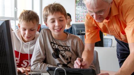 Unterricht mit Tablets ist eine interessante Neuerung im Schulalltag. Das Bild zeigt (von links) Johannes und Leroy aus der siebten Klasse der Realschule mit Thomas Kempf, der bei der Einführung behilflich ist.