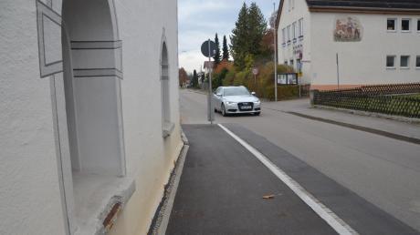 Die Engstelle durch den neuen Gehsteig an der Kirche in Tiefenbach gestattet nur einspuriges Durchfahren, bietet aber auch Schutz für das denkmalgeschützte Gebäude. Rechts das Bürzle-Haus als Schwerpunkt der Dorferneuerung.