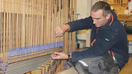 Orgelbauer Stefan Heiß in Aktion: Die Mechanik der Orgel wird reguliert. Diese Mechanik verbindet quasi die Tastengriffe des Organisten mit den Ventilen hinter den Pfeifen.