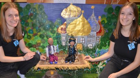 Sie ziehen bei dem Märchen maßgeblich die Fäden: Dorothee Flüs mit der Marionette des Dieners Aladin und Aurelia Koch, die den Prinzen Achmed führt. Im Hintergrund eines der Bühnenbilder, die Noah Khan gemalt hat.
