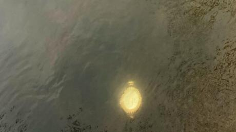Golden schimmerten die gestohlenen Gefäße im Mühlbach: Kirchenmitarbeiter Dieter Brocke hat das Diebesgut im Wasser entdeckt, Alexander Sassmann von der Fischereigemeinschaft hat es anschließend geborgen.