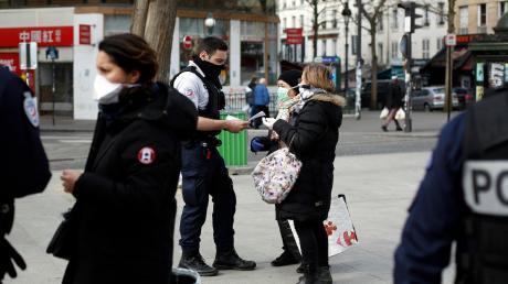 Ein Polizeibeamter kontrolliert am Eingang eines Marktes in Paris Passanten. Auch in Weißenhorns Partnerstadt Villecresnes, 20 Kilometer außerhalb der Hauptstadt gelegen, gelten wie überall in Frankreich sehr strenge Ausgangsbeschränkungen.