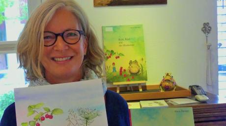 """Maria Barnett mit ihrem ersten Kinderbilderbuch """"Rubi, Karl und die Himbeeren"""" und mit einer Zeichnung aus ihrem zweiten Buch, in dem die Geschichte fortgesetzt wird."""