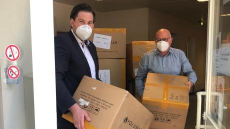 Rolf Gramm (rechts) übergibt Masken an Alexander Paul von der  Theresia-Hecht-Stiftung. Seine Zulieferer in China haben ihm 40000 Exemplare geschickt.