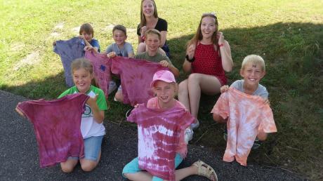 Die Kinder freuen sich über ihre gelungenen Batik-T-Shirts. Hinten im Bild die Betreuerinnen Marlene Geiselmann (links) und Aurelia Koch.