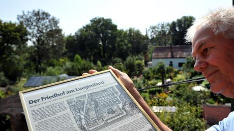 Werner Schindel hält in einer Kleingartenanlage in Augsburg einen Zeitungsausschnitt mit einem historischen Kupferstich des Geländes. In der kleinen Schrebergartenanlage mitten in Augsburg hegen und pflegen Hobbygärtner seit Jahrzehnten ihre Parzellen. Doch noch vor gut 200 Jahren war das Gelände ein Friedhof. dpa