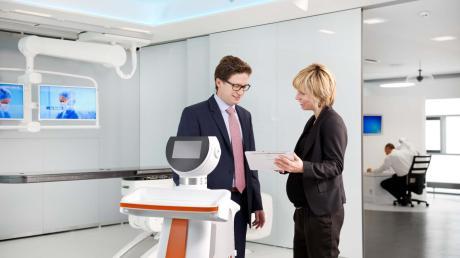 Dr. Tim Guhl und Christine Vogel im Medizin-Showroom von KUKA: Roboter im medizinischen Anwendungsbereich als Beispiel für innovative Entwicklungen am Augsburger Standort.