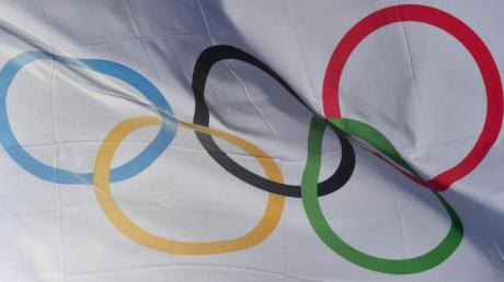 Eine Flagge mit den Olympischen Ringen weht im Wind. Die Winterspiele werden seit 1924 ausgetragen. Foto: Peter Kneffel