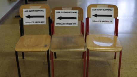 Auf Stühle aufgeklebte Zettel weisen in einem Wahllokal den Weg zur Stimmabgabe.
