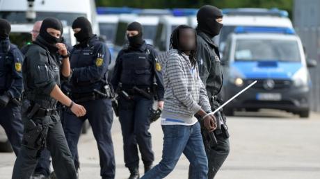 In der Flüchtlingsunterkunft in Ellwangen wird der 23-jährige Togoer im Rahmen eines Großeinsatzes der Polizei von maskierten Beamten abgeführt.