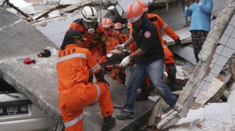 Rettungskräfte tragen einen Verletzten aus den Trümmern eines Restaurants, das durch das Erdbeben und den darauf folgenden Tsunami zerstört wurde.