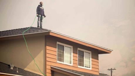 Ein Mann steht mit einem Gartenschlauch in der Hand auf dem Dach seines Hauses.