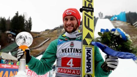 Markus Eisenbichler jubelt mit Pokal über seinen zweiten Platz.