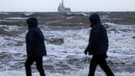 Spaziergänger sind in Warnemünde an der aufgewühlten Ostsee unterwegs.