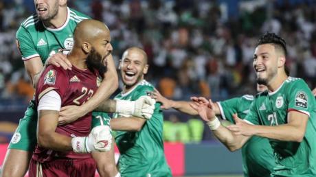 Algeriens Keeper Rais M'Bolhi(l) feiert mit seinen Teamkollegen das gegen Elfenbeinküste gewonnene Elfmeterschießen.