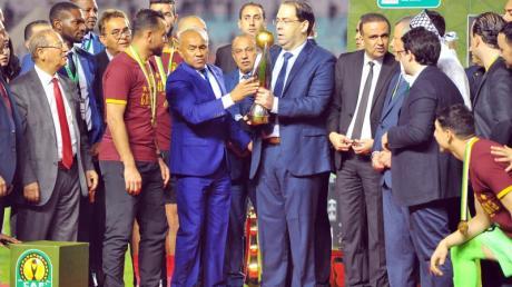 Tunesiens Premierminister Youssef Chahed (M/r) und CAF-Präsident Ahmad Ahmad überreichen den Pokal an Moez Ben Cherifia, Kapitän von Esperance Tunis.