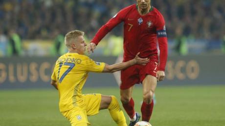 Oleksandr Sintschenko (l) aus der Ukraine und Cristiano Ronaldo aus Portugal kämpfen um den Ball. Foto: Efrem Lukatsky/AP/dpa