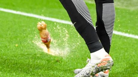 Eine fast voll Getraänkeflasche landet neben dem Leipziger Christopher Nkunku im Groupama Stadion auf dem Spielfeld.