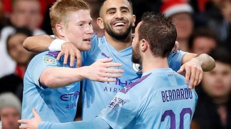 Riyad Mahrez (M) von Man City feiert mit seinen Teamkollegen Kevin De Bruyne (l) und Bernardo Silva den zweiten Treffer seines Teams.