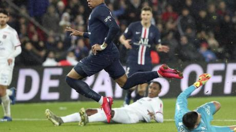 Paris Kylian Mbappe (M) erzielt gegen Lyons Torhüter Anthony Lopes (r) das zweite Tor seiner Mannschaft.