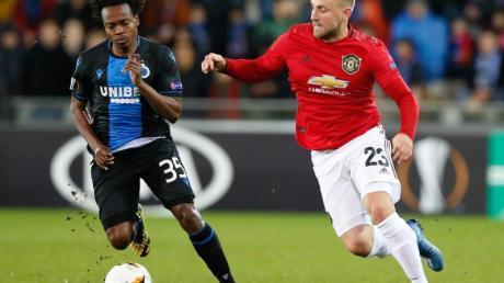 Percy Tau (l) vom FC Brügge und Luke Shaw von Manchester United kämpfen um den Ball.