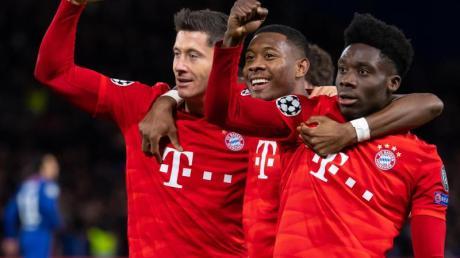Torschütze Robert Lewandowski (l-r), David Alaba und Alphonso Davies jubeln über das 3:0 in London.