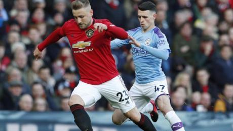 Manchester Uniteds Luke Shaw (l) setzt sich im Zweikampf gegen Phil Foden von Manchester City durch.