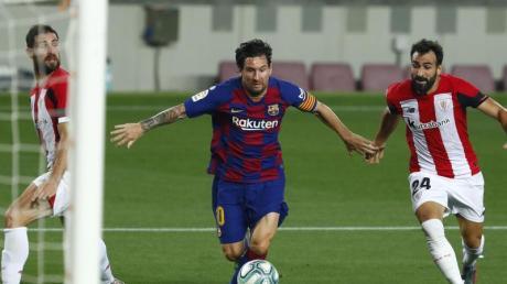 Lionel Messi (M) vom FC Barcelona wird von Bilbaos Mikel Balenziaga (r) bedrängt.