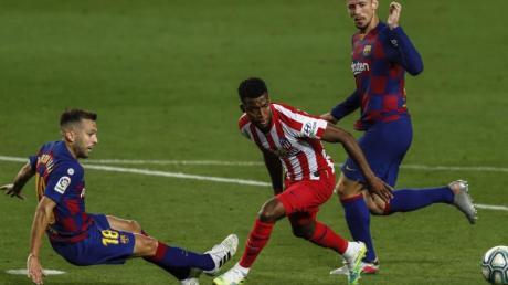Jordi Alba (l) und Clement Lenglet (r) vom FC Barcelona gegen Thomas Lemar von Atletico Madrid.