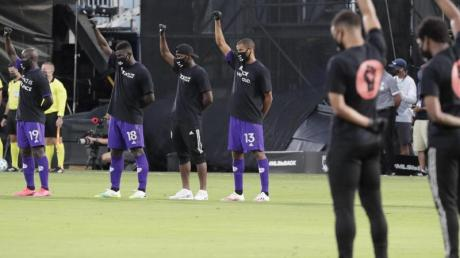 Orlando-Spieler heben vor dem Spiel ihre Fäuste als Zeichen gegen Rassismus.
